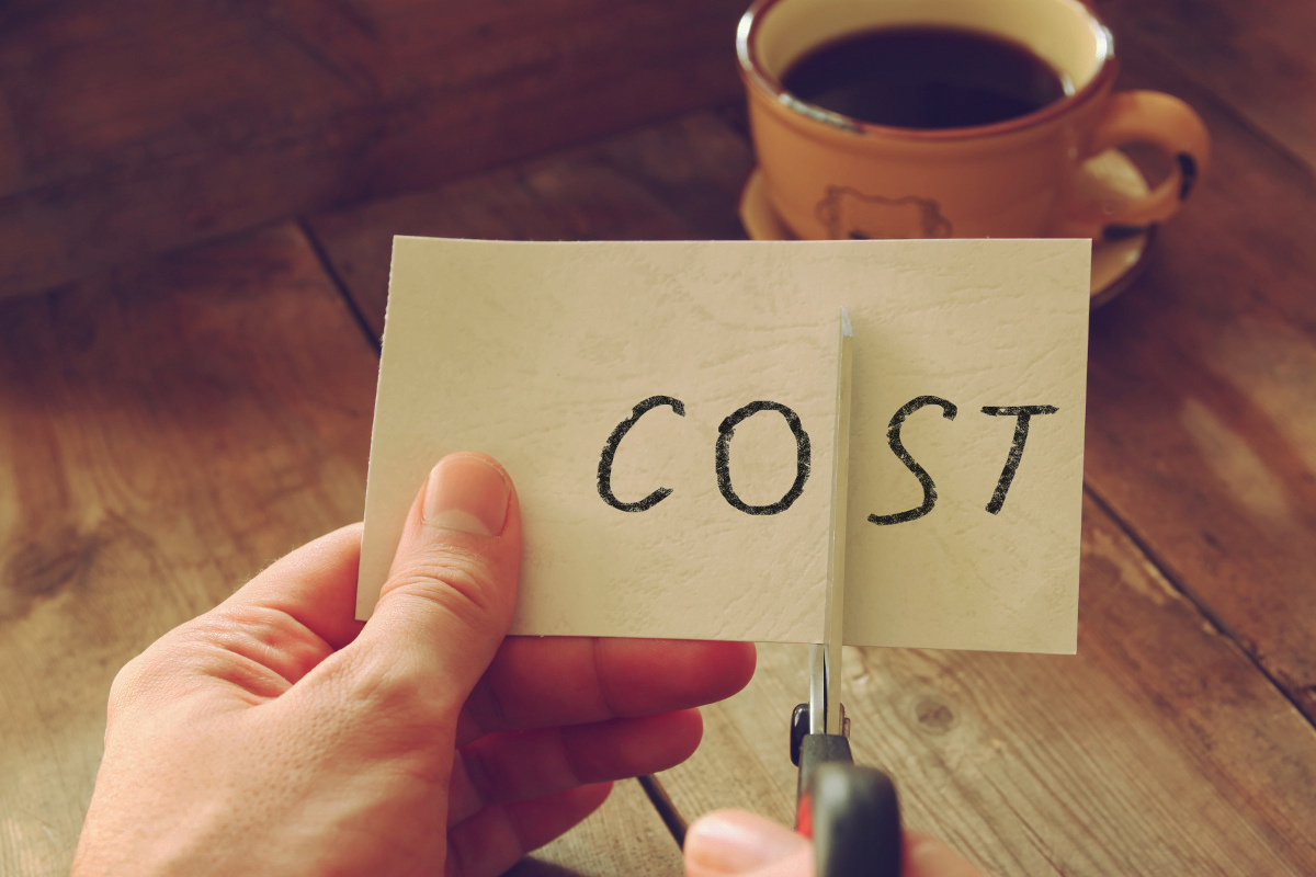 Hands Using Scissors to Cut Paper with the Word 'Cost' on Blurred Background with Cup of Coffee