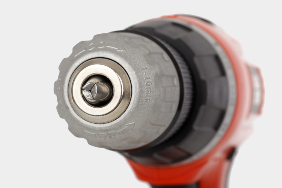Close Up of Orange Power Drill Isolated on Gray Background