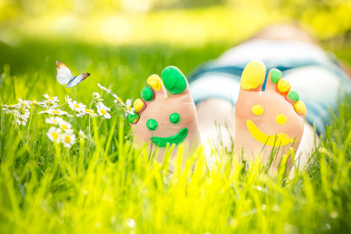 Child Lying on Green Grass with Smiley Faces Painted on Feet