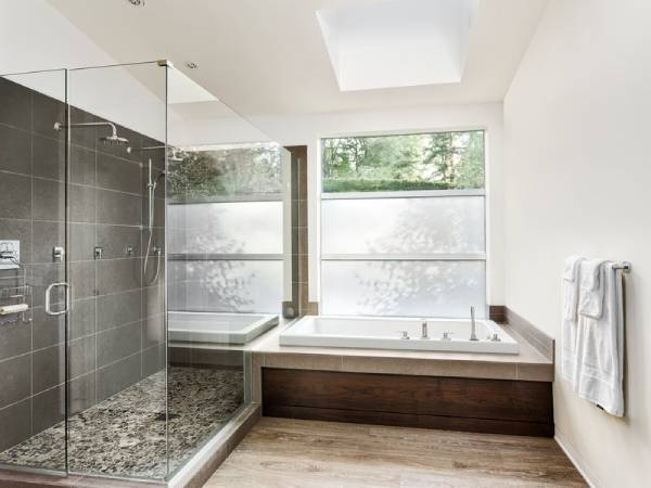 Master bathroom with a nice soaking tub and clear glass shower