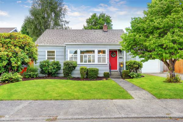 Craftsman style house with blue paint, red door, and nicely manicured yard