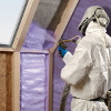 Person in Full Protective Suit Spraying Foam Insulation Between Wall Studs